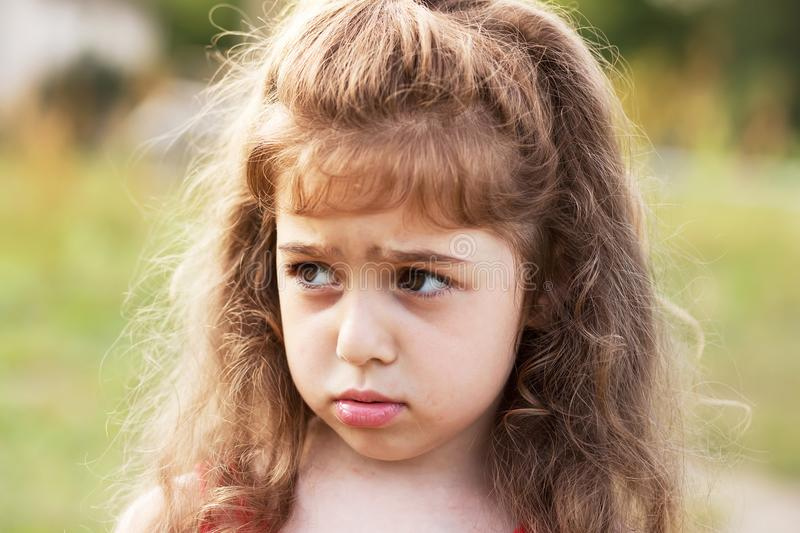 Unhappy beautiful little Girl is crying outdoors royalty free stock photography