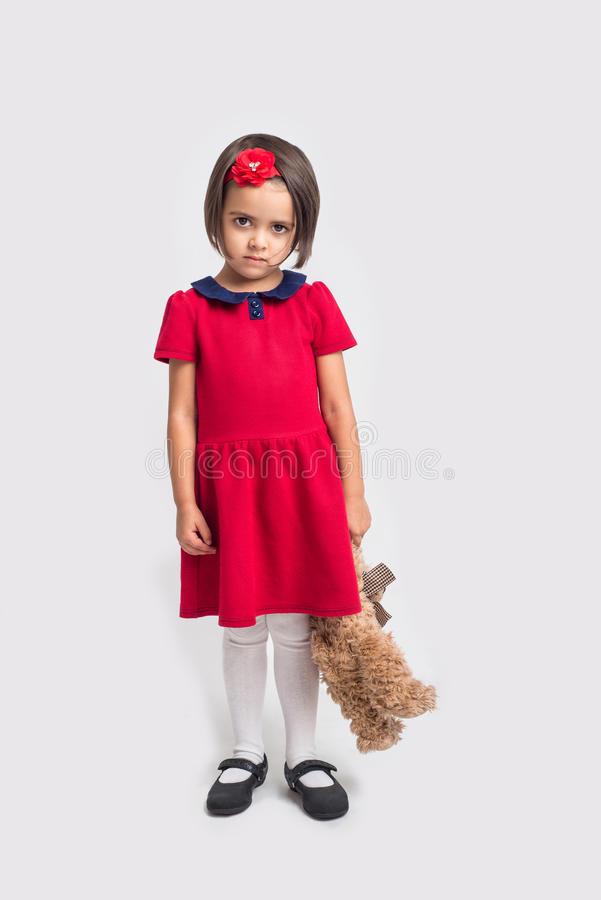 Unhappy beautiful little girl in a red dress with a toy bear. Studio shot royalty free stock photo