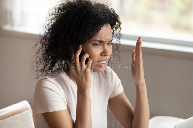 Unhappy biracial woman having unpleasant cellular call. Unhappy african American millennial woman talk on smartphone upset hearing bad negative news stock photography