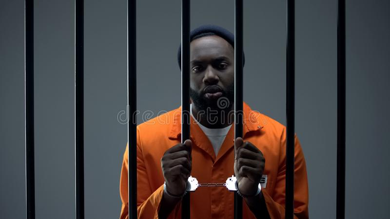 Unhappy black prisoner showing handcuffs, innocent male waiting for justice royalty free stock images
