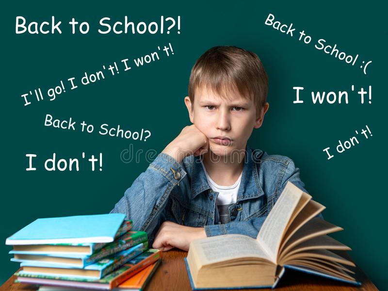 Unhappy boy of European appearance is sitting on the background of the school green board. Teen does not want to school. A stack royalty free stock images