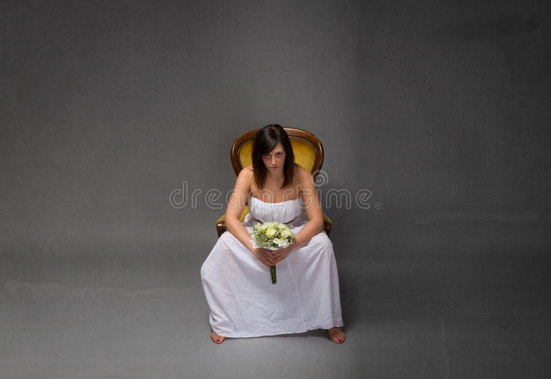 Unhappy bride sitting with bouquet on hand. Dark background stock images