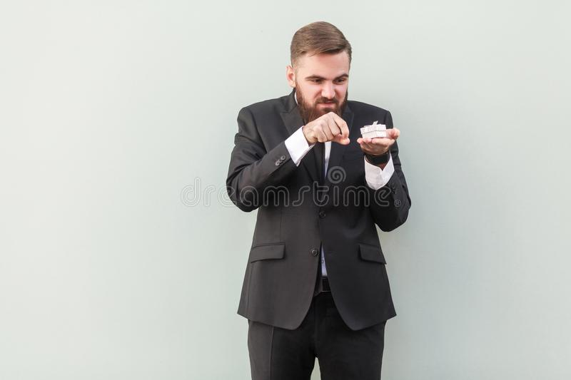 Unhappy business man, throws out small gift box. Studio shot, gray background stock images