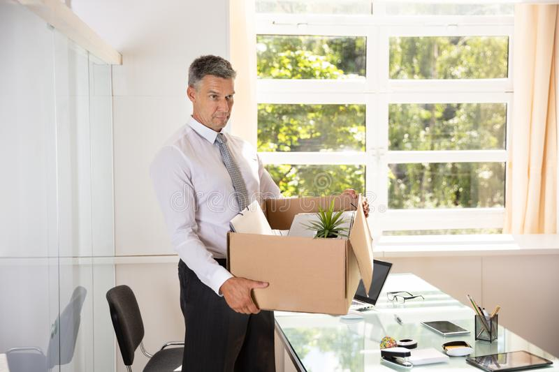 Unhappy Businessman Carrying Belongings In Cardboard Box. Unhappy Mature Businessman Carrying Belongings In Cardboard Box At Workplace stock images