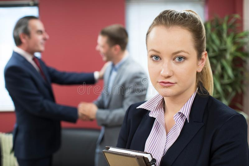 Portrait Of Unhappy Businesswoman With Male Colleague Being Cong stock photography