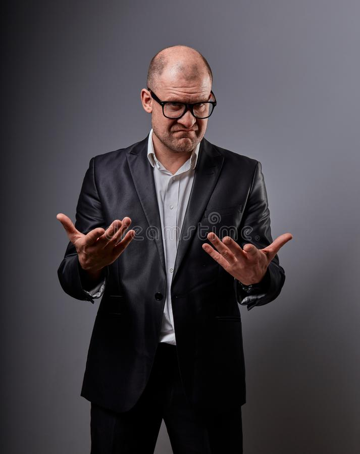 Unhappy busuness man in black suit and glasses showing the palm calling and promote sign on grey background. Closeup. Portrait stock image