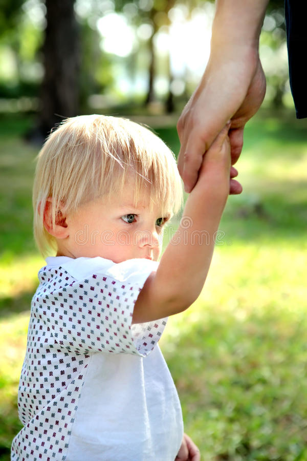 Unhappy Child hold the Parent Hand stock photography