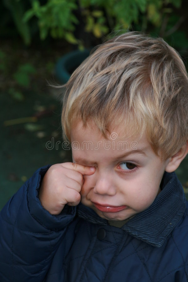 Unhappy child rubbing eye. Portrait of unhappy young boy rubbing eye with finger royalty free stock image