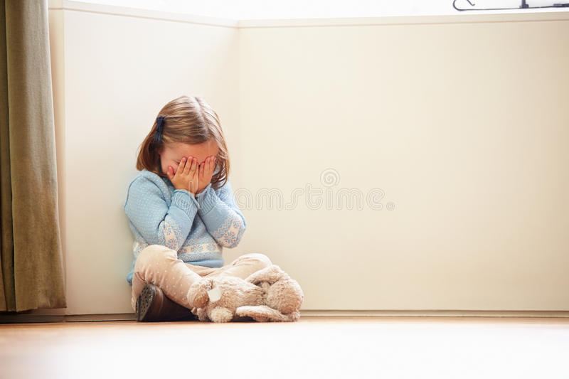 Unhappy Child Sitting On Floor In Corner At Home. Unhappy Young Child Sitting On Floor In Corner At Home