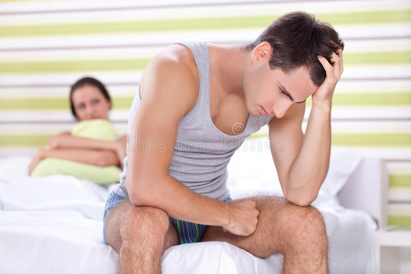 Unhappy couple in bedroom. Unhappy young couple with problem in bedroom royalty free stock photo