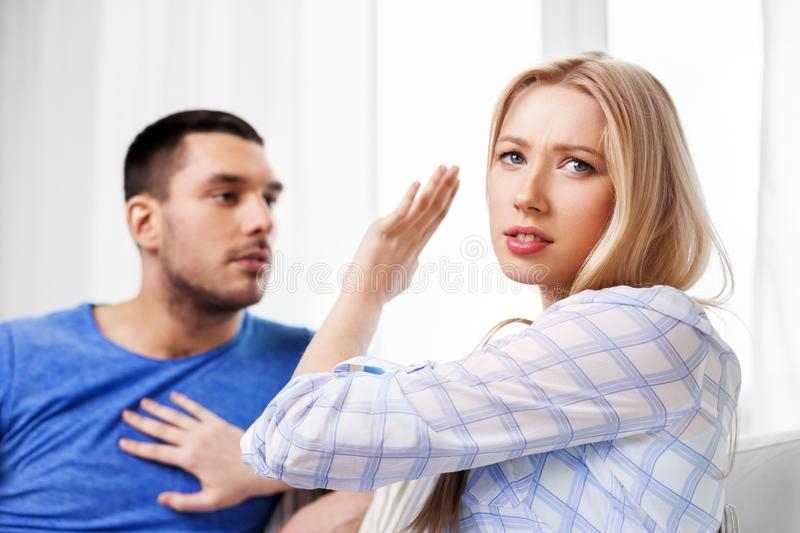 Unhappy couple having argument at home. People, relationship difficulties, conflict and family concept - unhappy couple arguing at home royalty free stock images