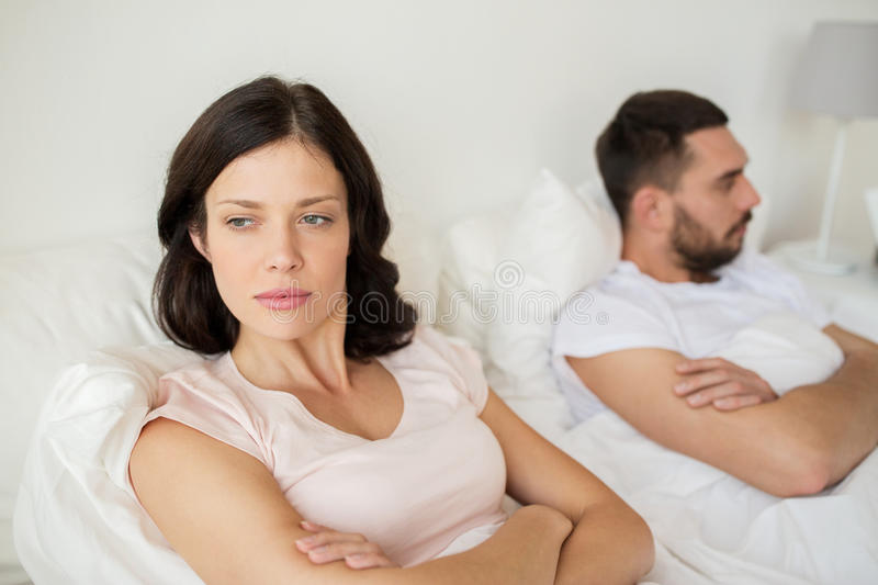 Unhappy couple having conflict in bed at home. People, relationship difficulties and family concept - unhappy couple having conflict in bed at home royalty free stock photography