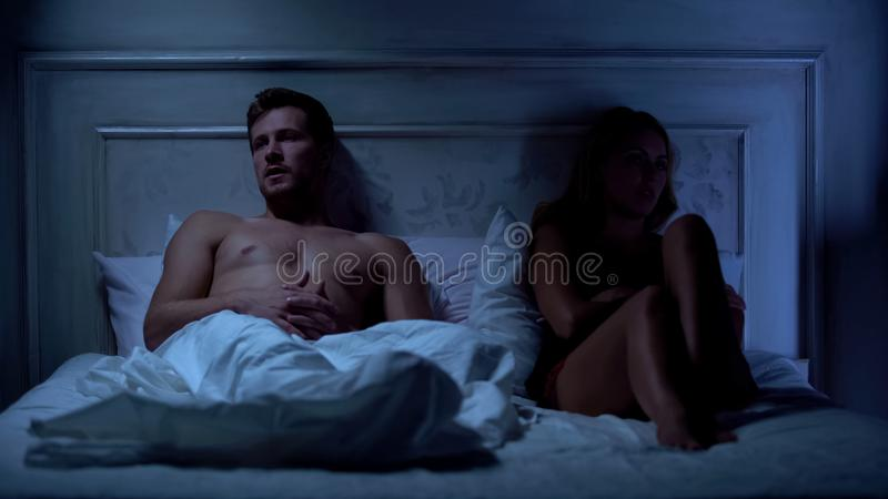 Unhappy couple having conflict in bed, relations difficulties, misunderstanding. Stock photo stock photos