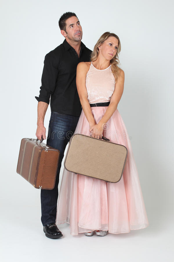 Unhappy Couple Holding Suitcases stock photos