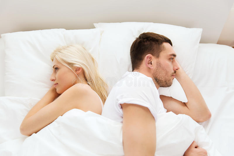 Unhappy couple lying in bed at home. People, relationship difficulties, conflict and family concept - unhappy couple lying back to back in bed at home royalty free stock photography