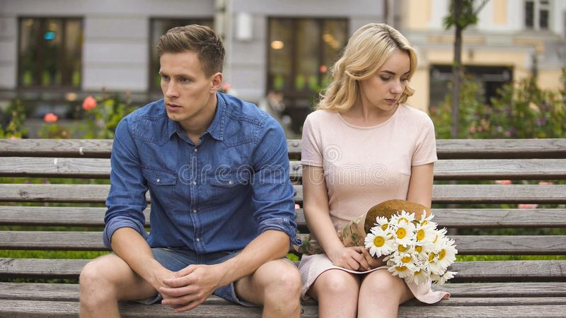 Unhappy couple sitting after fight, girl with flowers, problem in relationship royalty free stock image