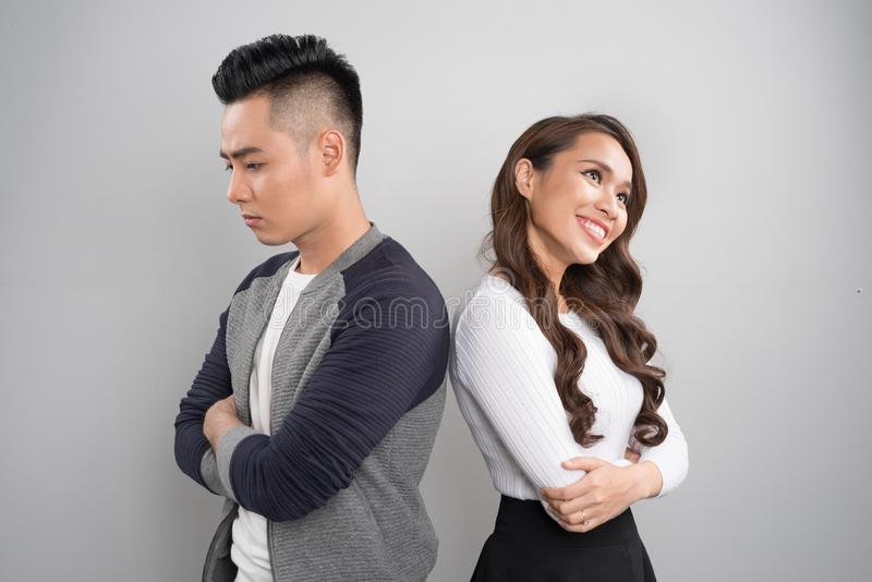 Unhappy couple standing back to back in a studio royalty free stock images