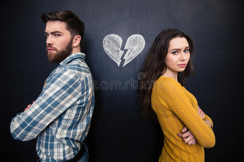 Unhappy couple standing over chalkboard background with drawn broken heart. Unhappy young couple standing with arms crossed over background of chalkboard with royalty free stock photo