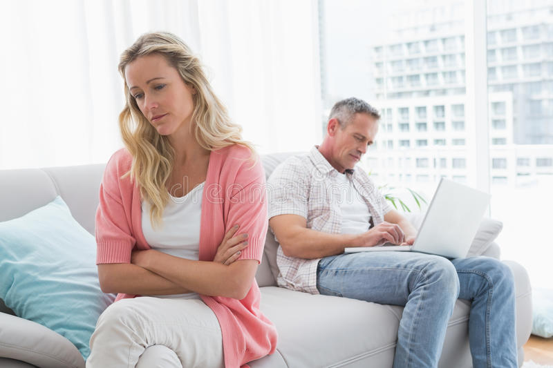 Unhappy couple are stern and having troubles. At home in the living room royalty free stock image