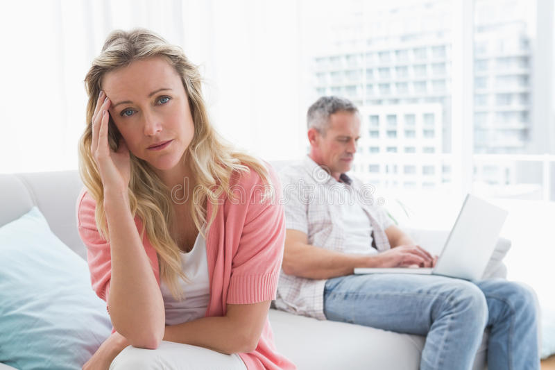 Unhappy couple are stern and having troubles. At home in the living room stock image