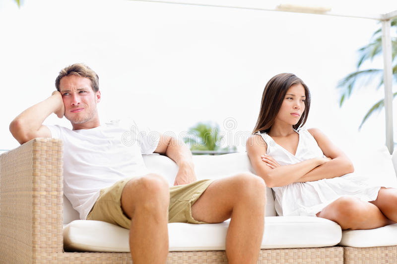 Unhappy couple upset with marital problems. Angry and mad having conflict after argument. Young multiracial couple, Asian woman, Caucasian white man royalty free stock photos