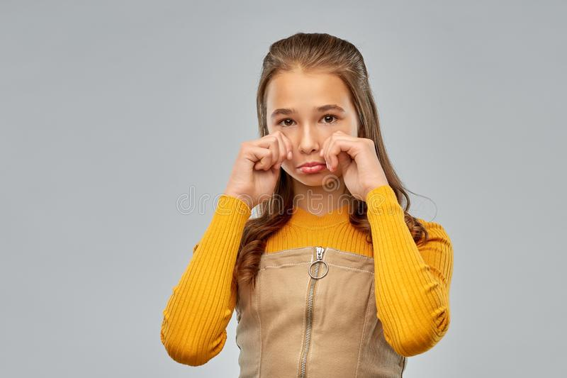 Unhappy crying teenage girl over gray background royalty free stock photography