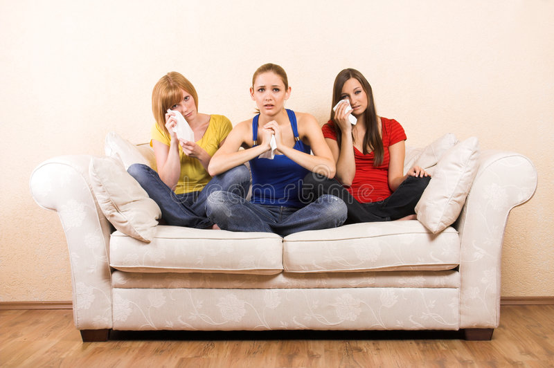 Unhappy crying women on a sofa royalty free stock image