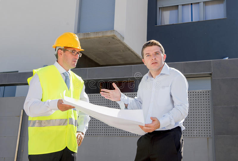 Unhappy customer in stress and constructor foreman worker arguing outdoors on new house building blueprints. Unhappy customer in stress and constructor foreman royalty free stock photography