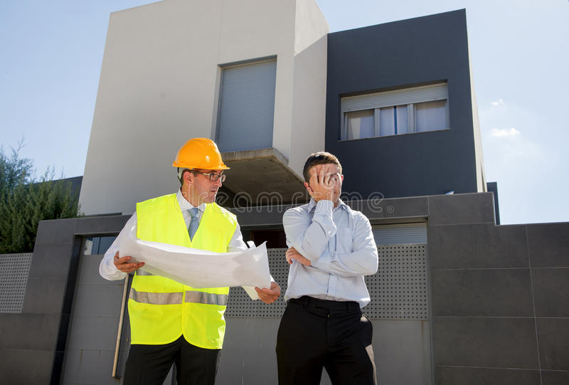 Unhappy customer in stress and constructor foreman worker with helmet and vest arguing outdoors on new house building blueprints. In real state business royalty free stock photos