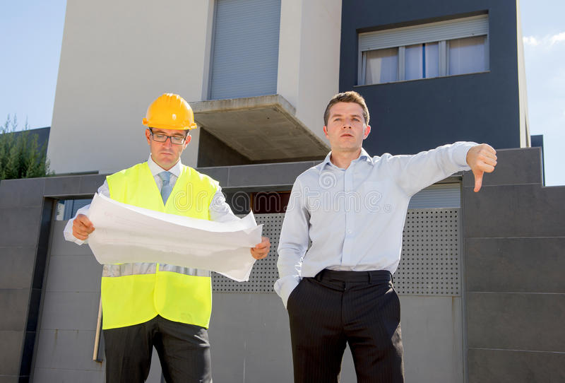 Unhappy customer in stress and constructor foreman worker with helmet and vest arguing outdoors on new house building blueprints. In real state business stock photos