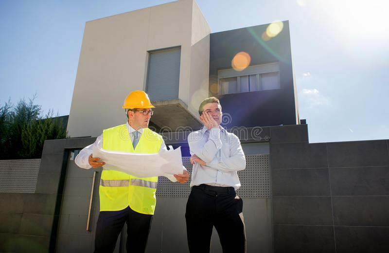 Unhappy customer in stress and constructor foreman worker with helmet and vest arguing outdoors on new house building blueprints. In real state business stock photography
