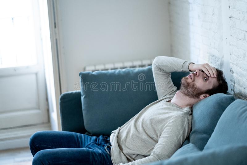 Young man suffering from depression hopeless and alone at home. Unhappy depressed caucasian male sitting and lying in living room couch feeling desperate a stock images