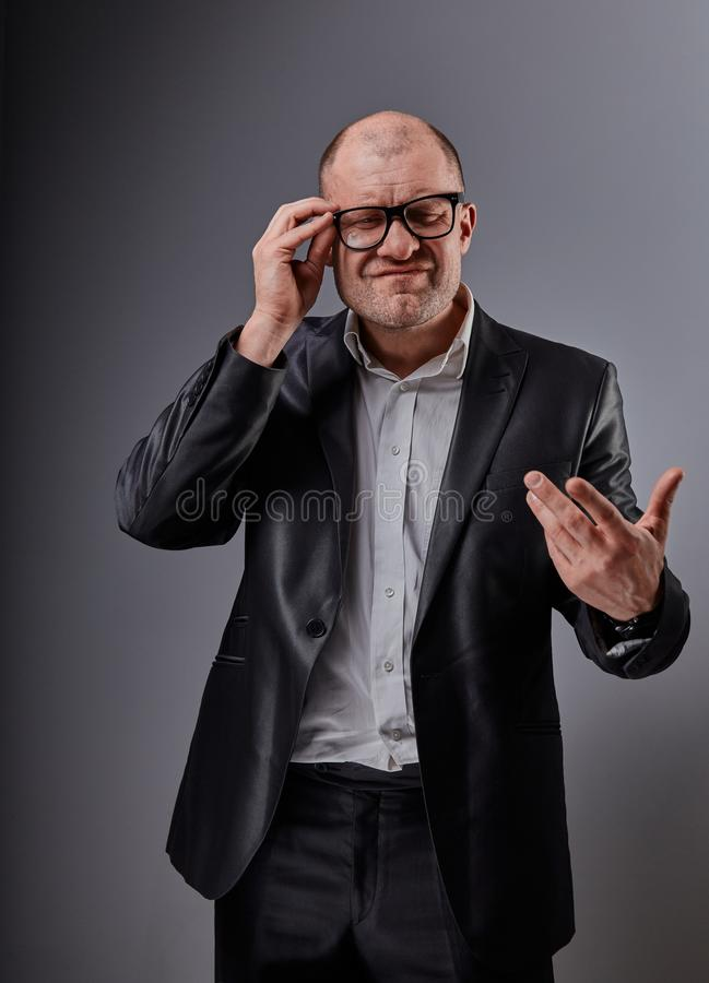Unhappy depressed gesticulating busuness man in black suit and glasses grimacing on grey background. Closeup stock image