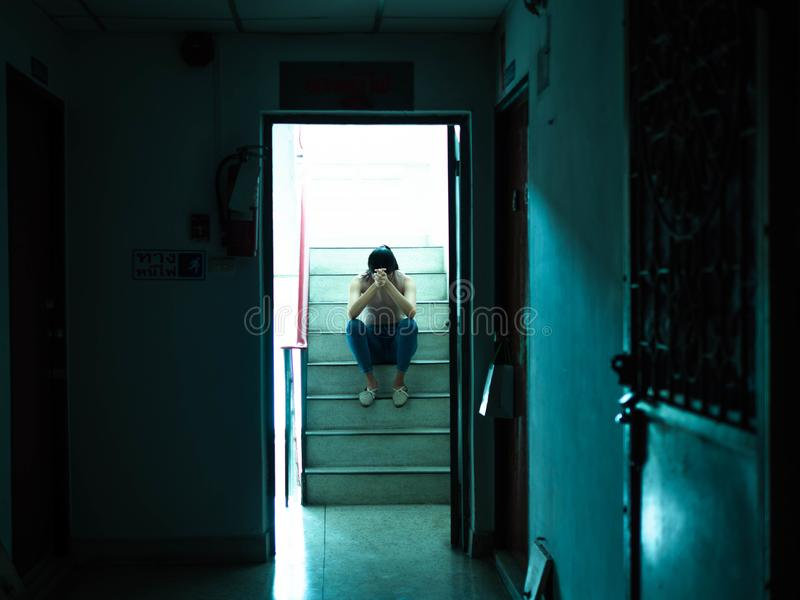 Unhappy depressed teenager with face in hands sitting stair, thinking about problem with relationships or work, feeling despair. And anxiety, loneliness, having stock photography