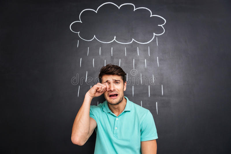 Unhappy disappointed young man crying under the drawn rain stock photography