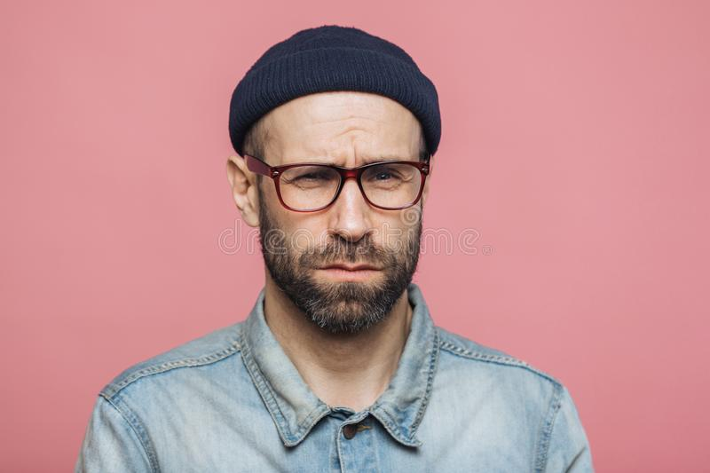 Unhappy discontent unshaven male looks with grumpy expression into camera, wears glasses black hat and stylish denim shirt, isolat stock images