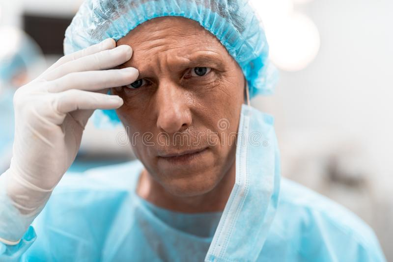 Unhappy doctor looking and touching his forehead royalty free stock photos