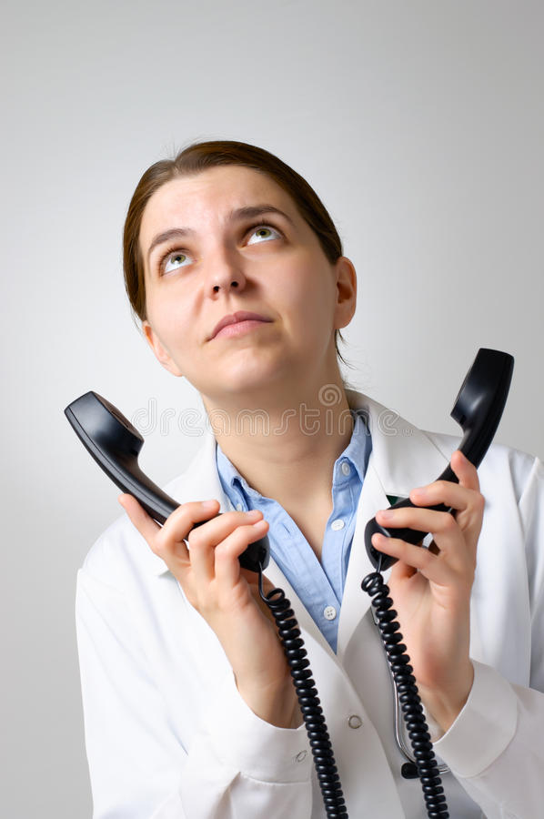 Unhappy doctor with phone receivers. Annoyed female doctor with two phone receivers royalty free stock image