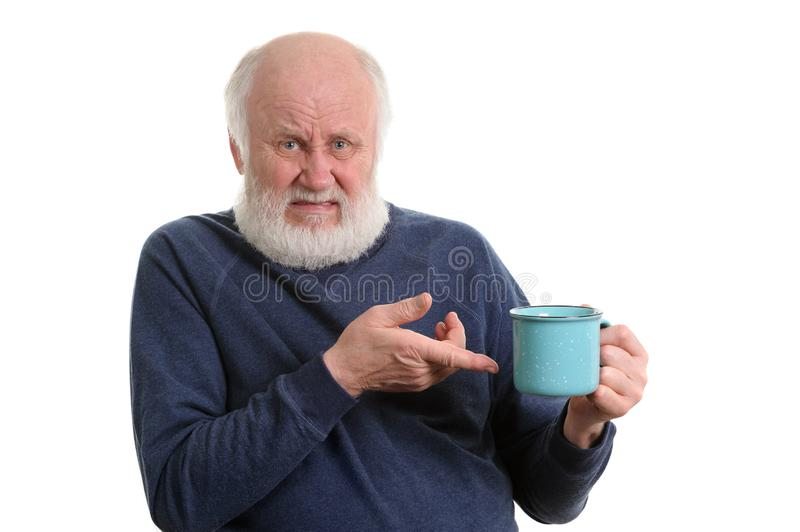 Unhappy elderly man with cup of bad tea or coffee isolated on white. Unhappy elderly grey haired man with blue cup of tea or coffe isolated on white stock images