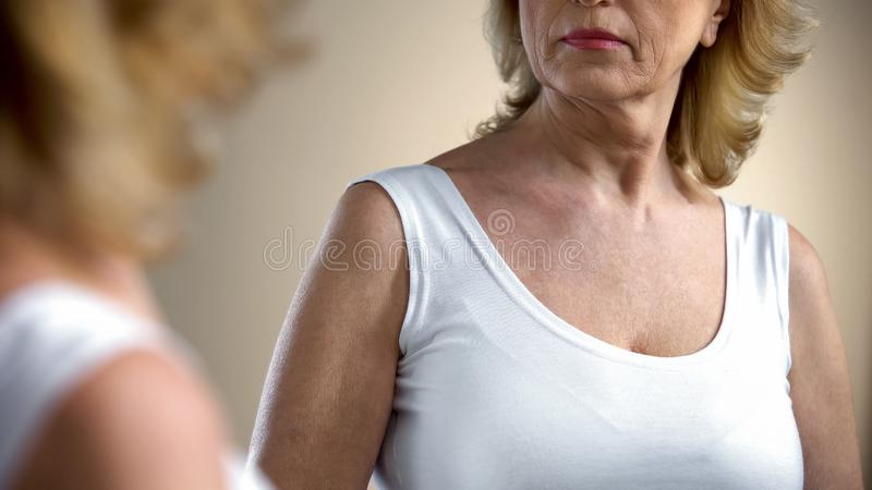 Unhappy elderly woman looking at her body in mirror, lost beauty, wrinkles royalty free stock images