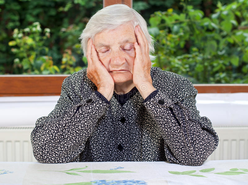 Unhappy elderly woman. Sitting at the table royalty free stock photos