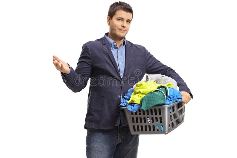 Unhappy elegant guy holding a laundry basket filled with clothes royalty free stock image