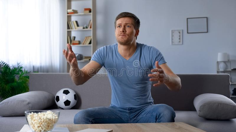 Unhappy fan, man upset about defeat of football team, watching tv broadcast. Stock photo stock photo