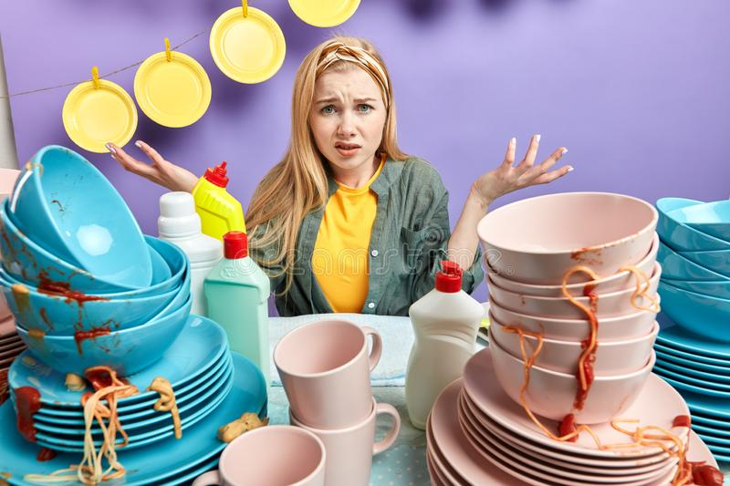Unhappy female shrugging shoulders being sad not knowing how to wash the dishes. Emotion and feeling concept. close up portrait stock photo
