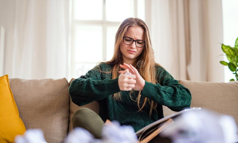 An unhappy female student sitting on sofa, studying. An unhappy, sad and frustrated female student sitting on sofa, studying stock photography
