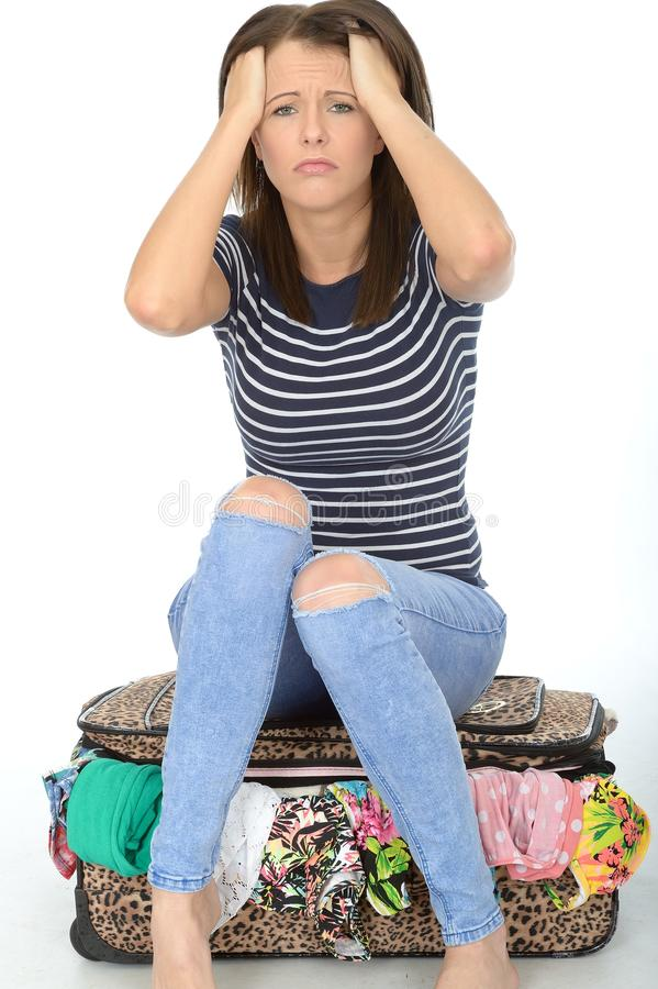 Unhappy Frustrated Attractive Young Woman Sitting on an Overflowed Suitcase royalty free stock photos