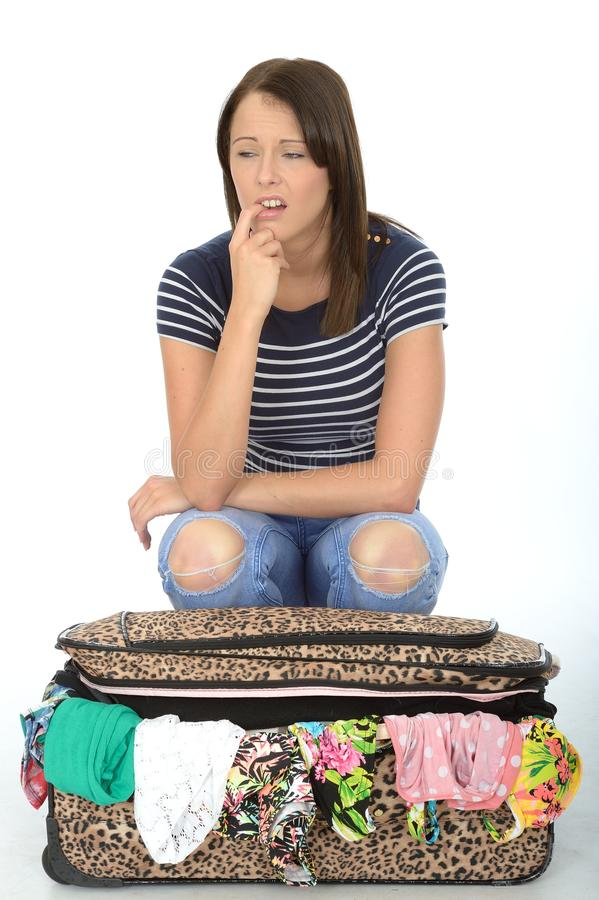 Unhappy Frustrated Attractive Young Woman Sitting on an Overflowing Suitcase royalty free stock photography