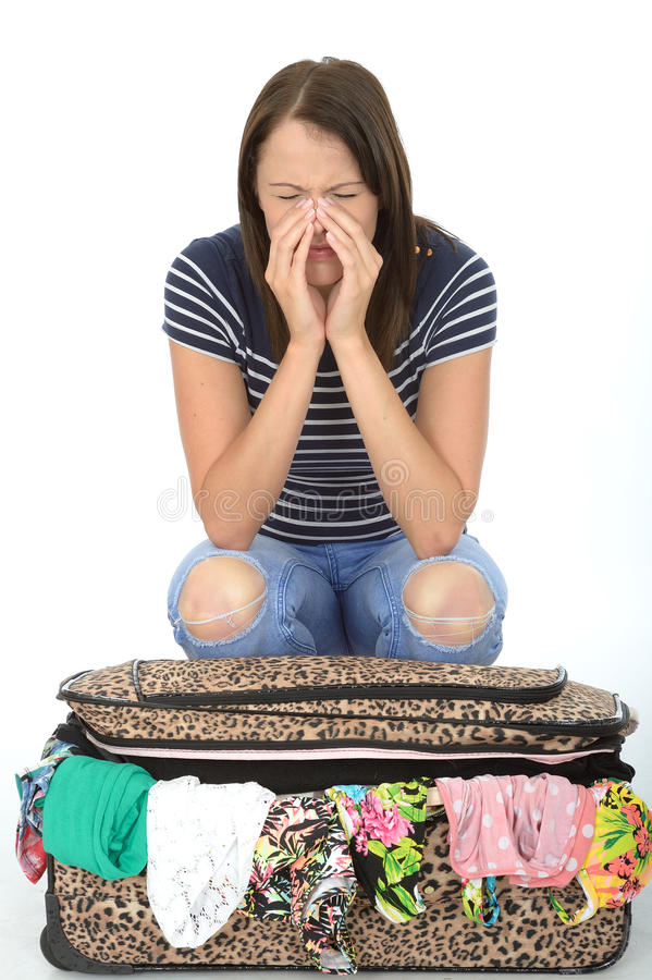 Unhappy Frustrated Attractive Young Woman Sitting on an Overflowing Suitcase stock photo
