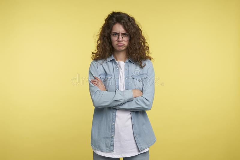 Unhappy funny brunette woman with curly hair, over yellow background royalty free stock photography