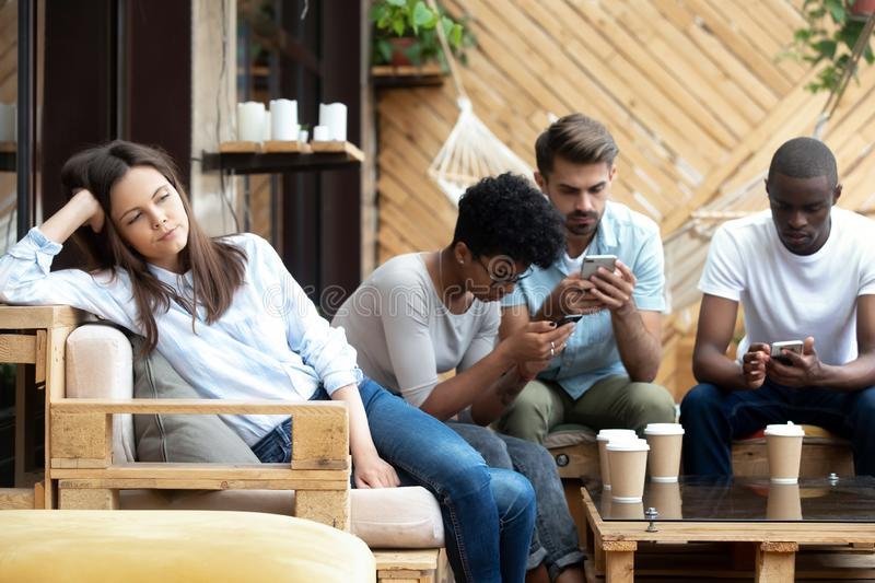Unhappy girl feel bored with addicted to gadgets friends stock image